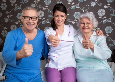 group of seniors and caregiver doing thumbsup