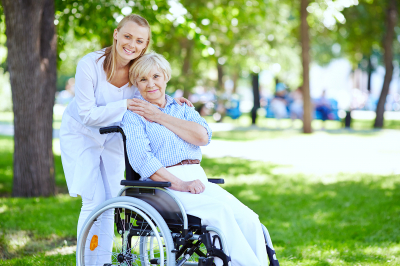 elderly woman in a wheelchair with her caregiver early morning in the park